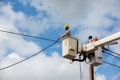 Electricians repairing wire of the power line on electric power. Pole stock images