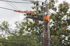 Electricians repairing wire of the power line on electric power. Pole stock image