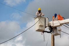 Electricians repairing wire of the power line on electric power. Pole Royalty Free Stock Photo