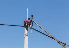 Electricians repairing wire of the power line on electric power pole Royalty Free Stock Photos