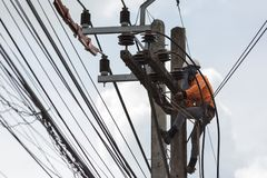 Electricians repairing wire of the power line on electric power. Pole stock photo