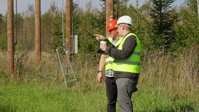 Electricians talking at outdoors near electrical posts stock video