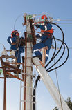 Electricians troubleshoot on power lines. Electricians working on the support of power transmission lines with modern appliances troubleshooting damage Royalty Free Stock Images
