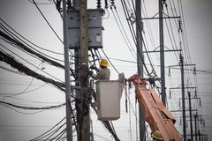 Electricians Wiring Cable repair services. Technician checking fixing broken electric wire on pole. Electricity power utility worker in crane truck bucket stock photography