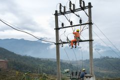 Electricians working high on electricity pole in Vietnam.  stock photos