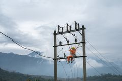 Electricians working high on electricity pole in Vietnam.  royalty free stock images