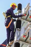 Electricians working on high voltage power lines stock image