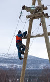 Electricians working on a pole in winter Stock Photo