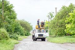 Electricians working on poles, a. Group of workers in special vehicles, repairing electric transmission lines stock photos