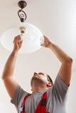 Electricista acabado montando la lámpara del techo Fotos de archivo libres de regalías