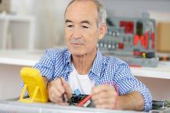 Electricista adulto mayor que usa la pluma eléctrica de la prueba imagenes de archivo