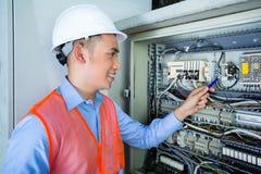 Electricista asiático en el panel en emplazamiento de la obra Fotos de archivo libres de regalías