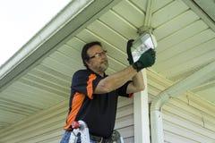 Electricista Changing un bulbo en una lámpara exterior Imágenes de archivo libres de regalías