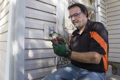 Electricista Checking Outside Outlet para el cliente Imagen de archivo