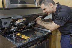 Electricista Checking una gama de Stovetop Imágenes de archivo libres de regalías