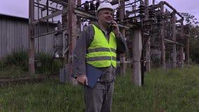 Electricista con smartphone y documentación que caminan en la subestación almacen de video
