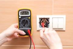 Electricista de la mano que comprueba voltaje Fotos de archivo libres de regalías