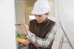 Electricista de sexo femenino joven que instala el zócalo eléctrico en la pared fotos de archivo