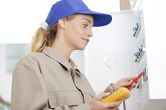 Electricista de sexo femenino que usa el mult?metro en el gabinete del disyuntor foto de archivo