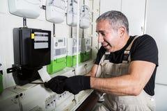 Electricista divertido que hace la reparación eléctrica en metro de la electricidad imagenes de archivo