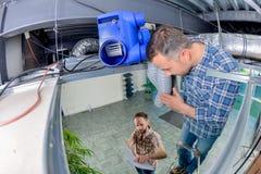 Electricista dos que trabaja en el panel de techo imagenes de archivo