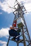 Electricista en el casco rojo que trabaja en polo de la energía eléctrica Foto de archivo