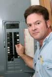 Electricista en el panel de los cortacircuítos Foto de archivo libre de regalías