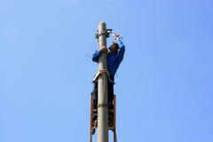 Electricista en el poste eléctrico de la torre Foto de archivo libre de regalías