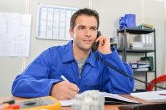 Electricista en el teléfono en oficina Imagenes de archivo