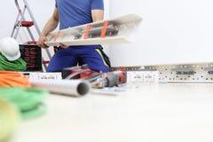 Electricista en el trabajo con el tubo plástico en su mano para pasar los cables eléctricos a los zócalos, circuitos eléctricos,  imagen de archivo libre de regalías