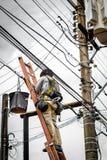 Electricista en polo eléctrico Imagenes de archivo