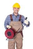Electricista feliz que sostiene el enchufe del alambre imagenes de archivo