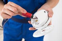 Electricista Holding Smoke Detector Foto de archivo libre de regalías