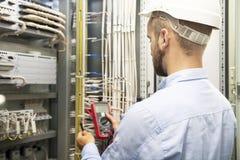 Electricista joven que trabaja en el panel eléctrico El ingeniero del electricista prueba instalaciones y los alambres eléctricos foto de archivo