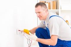 Electricista que comprueba el zócalo imagen de archivo