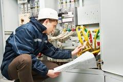 Electricista que controla la línea eléctrica de cableado Imágenes de archivo libres de regalías