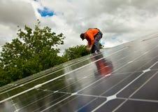Electricista que controla los paneles solares Imagenes de archivo
