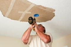 Electricista que instala la base ligera en techo Imagenes de archivo
