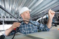 Electricista que instala los cables en tejado imagenes de archivo