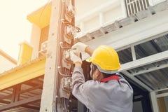 Electricista que instala un metro de poder fotos de archivo