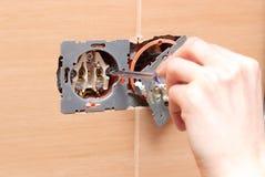 Electricista que instala un zócalo de poder Fotos de archivo