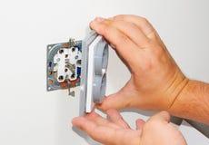 Electricista que instala un zócalo montado en la pared gris de la corriente ALTERNA con un destornillador en una pared blanca, re Foto de archivo