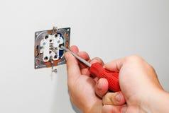 Electricista que instala un zócalo montado en la pared gris de la corriente ALTERNA con un destornillador en una pared blanca, re Fotografía de archivo
