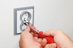 Electricista que instala un zócalo montado en la pared gris de la corriente ALTERNA con un destornillador en una pared blanca, re Fotografía de archivo libre de regalías