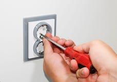 Electricista que instala un zócalo montado en la pared gris de la corriente ALTERNA con un destornillador en una pared blanca, re Foto de archivo libre de regalías