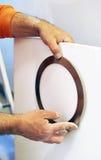 Electricista que instala una lámpara moderna en una placa del yeso para el techo de la cocina Imagenes de archivo