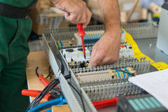 Electricista que monta el gabinete eléctrico industrial Imagen de archivo libre de regalías