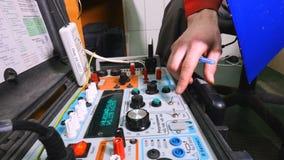 Electricista que prueba corriente eléctrica con el equipo especial en la fábrica industrial almacen de video
