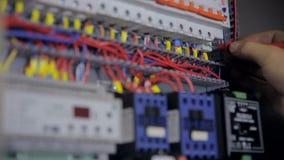 Electricista que prueba corriente eléctrica Voltaje industrial de la prueba del electricista de la fábrica usando multímetro en e almacen de video