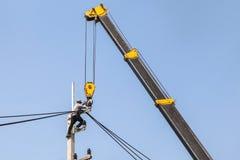 Electricista que repara el alambre de la línea eléctrica en polo de la energía eléctrica con la grúa Imagen de archivo libre de regalías
